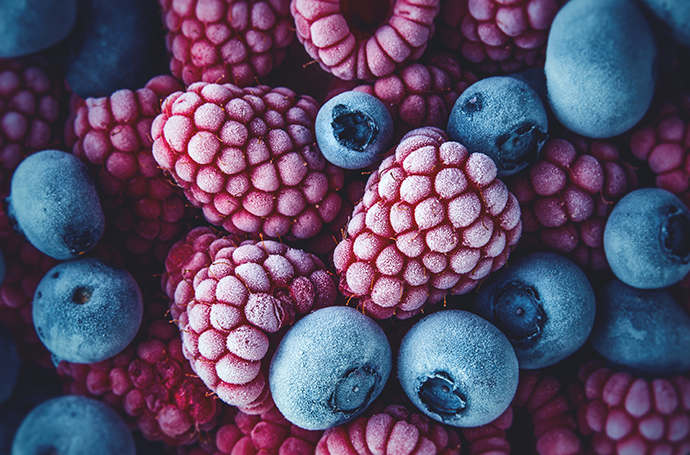Macro picture of a pile of frozen blueberries and raspberries