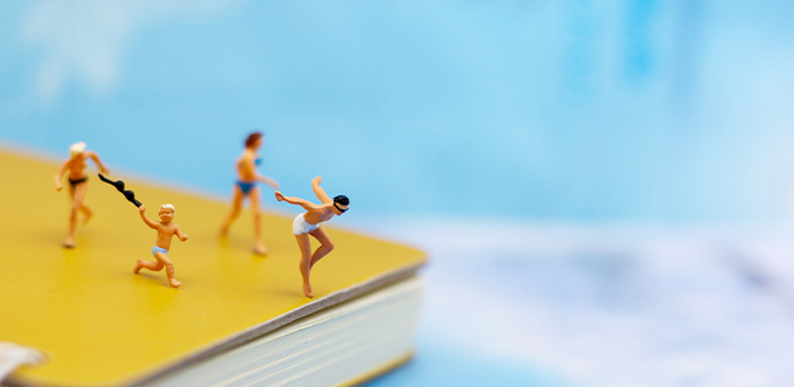 Tiny figurines, photographed in macro, playfully posed on a book