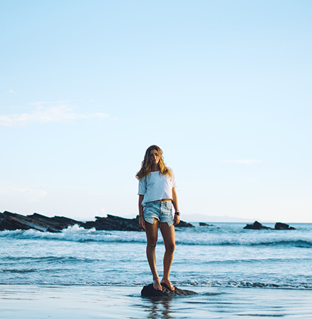 Leveraging the rule of thirds to photograph a woman standing on a rock in the ocean