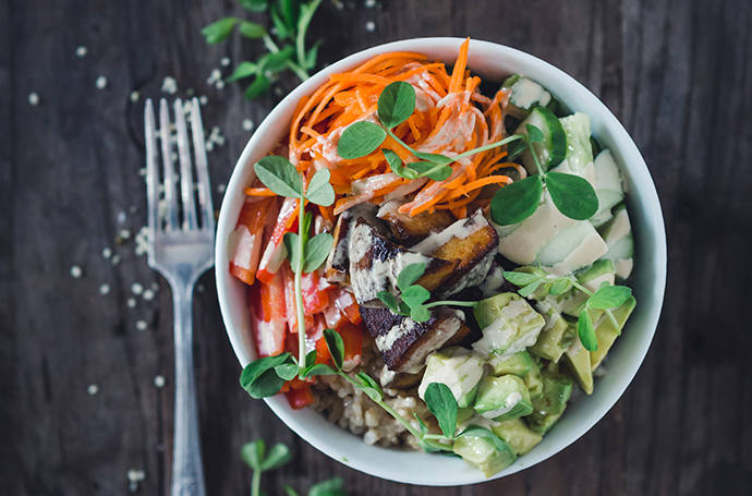 Staged food photo of a salad in white bowl with fork