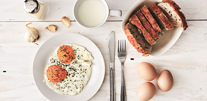 Simple food photograph of eggs over easy with milk and bread