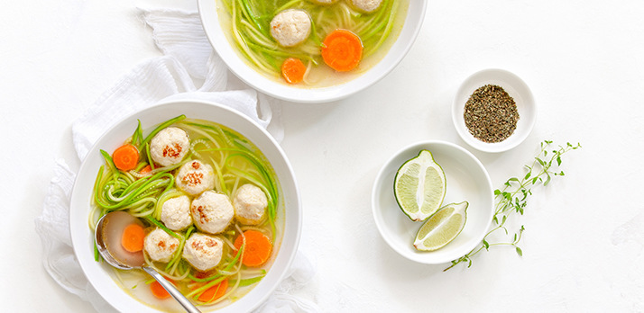 Artfully staged food picture of dumpling soup with limes and seasoning