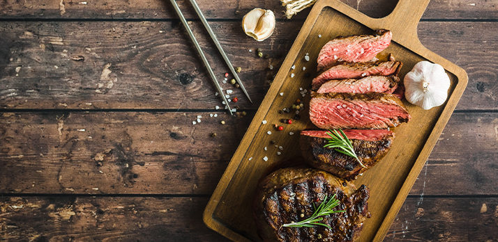 Savory food photo of a garlic and rosemary grilled steak on a cutting board