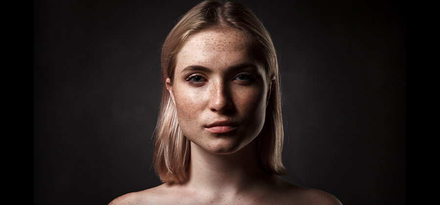 Portrait photo of woman with freckles on black background