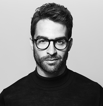 Black and white portrait headshot image of a bearded man in glasses