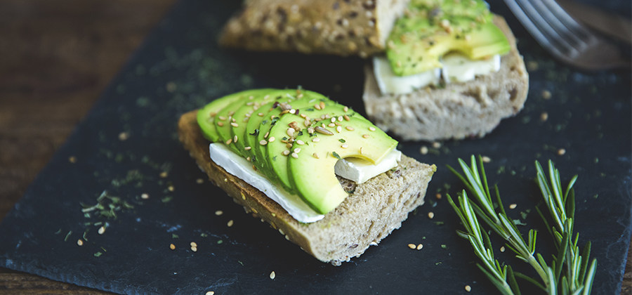 Mouth-watering image of an open-faced avocado and cream cheese sandwich