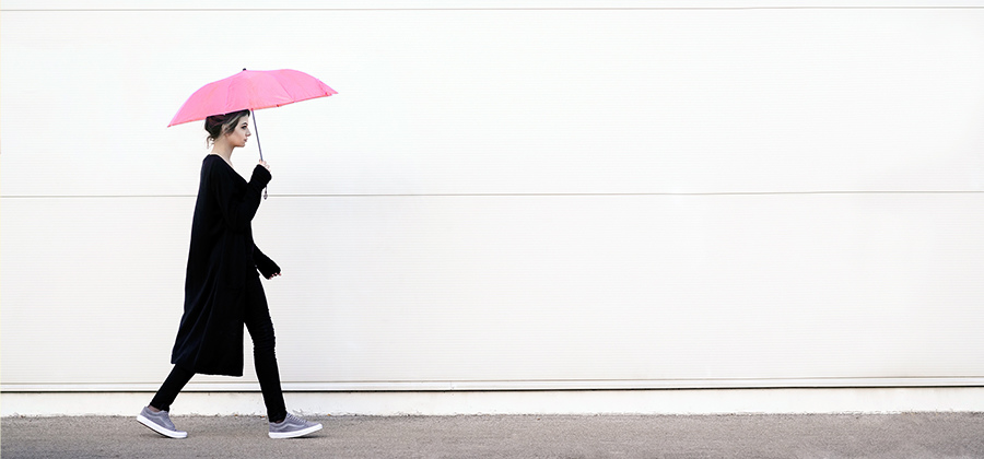 Using the rule of thirds to photograph a female walking with a pink umbrella